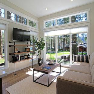 На фото: маленькая открытая гостиная комната в стиле кантри с серыми стенами, полом из винила и телевизором на стене без камина с