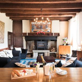 Idées déco pour un salon campagne de taille moyenne et ouvert avec un bar de salon, un mur blanc, une cheminée standard et un manteau de cheminée en pierre.