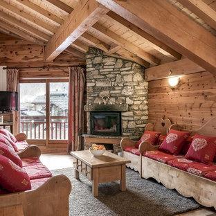 Aménagement d'un salon montagne de taille moyenne et ouvert avec une cheminée d'angle, un téléviseur indépendant, un mur marron, un sol en bois clair et un manteau de cheminée en pierre.