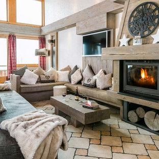 Idée de décoration pour un salon chalet ouvert avec un mur blanc, un poêle à bois, un téléviseur fixé au mur et un manteau de cheminée en bois.