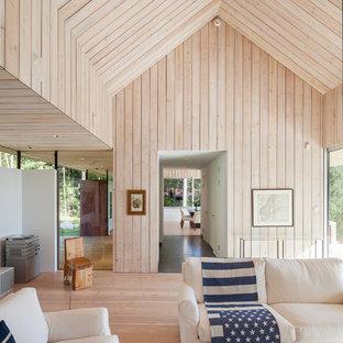 На фото: большая парадная, открытая гостиная комната в скандинавском стиле с светлым паркетным полом и бежевыми стенами без камина, ТВ с