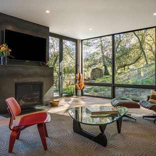 Example of a large trendy open concept medium tone wood floor living room design in San Francisco with a standard fireplace, a concrete fireplace and a wall-mounted tv
