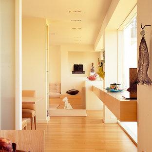 Imagen de salón para visitas abierto, moderno, grande, con paredes beige, suelo de madera clara y suelo naranja