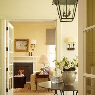 サンフランシスコの広いトラディショナルスタイルのおしゃれなLDK (濃色無垢フローリング、黄色い壁、標準型暖炉、漆喰の暖炉まわり) の写真