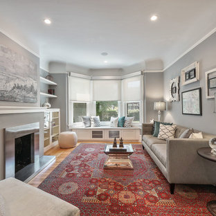 Example of a transitional medium tone wood floor and brown floor living room design in San Francisco with gray walls, a standard fireplace and a metal fireplace