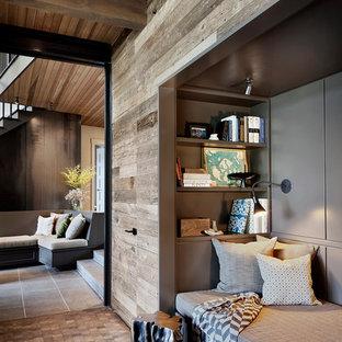 Großes, Fernseherloses, Offenes Uriges Wohnzimmer mit dunklem Holzboden, Kamin, Kaminumrandung aus Stein und schwarzem Boden in Seattle