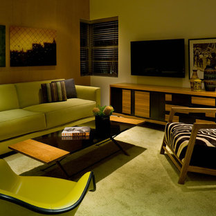 This is an example of a medium sized modern enclosed living room in Miami with a wall mounted tv, white walls and green floors.
