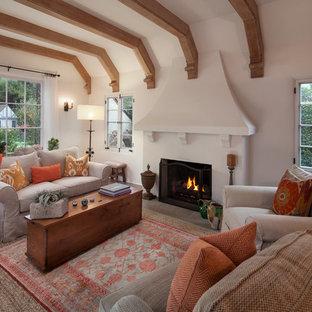 サンタバーバラのトランジショナルスタイルのおしゃれな独立型リビング (白い壁、無垢フローリング、標準型暖炉、漆喰の暖炉まわり、テレビなし) の写真