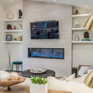 フェニックスの中サイズのミッドセンチュリースタイルのおしゃれなLDK (ベージュの壁、磁器タイルの床、標準型暖炉、タイルの暖炉まわり、壁掛け型テレビ、ベージュの床) の写真