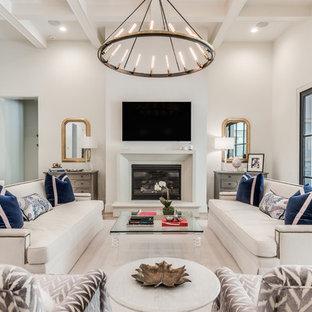 ヒューストンの巨大なトランジショナルスタイルのおしゃれなLDK (白い壁、淡色無垢フローリング、標準型暖炉、コンクリートの暖炉まわり、壁掛け型テレビ、ベージュの床) の写真