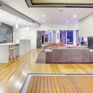 Immagine di un soggiorno minimal aperto con camino classico e pavimento giallo