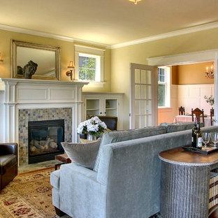 Mittelgroßes Klassisches Wohnzimmer mit gefliester Kaminumrandung, gelber Wandfarbe, braunem Holzboden und Kamin in Seattle