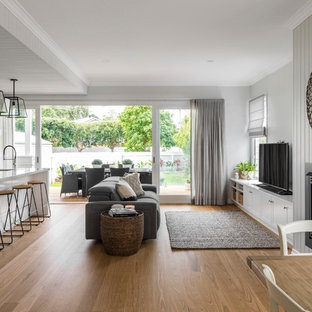 Transitional open concept living room in Brisbane with grey walls, medium hardwood floors, a standard fireplace, a freestanding tv and brown floor.