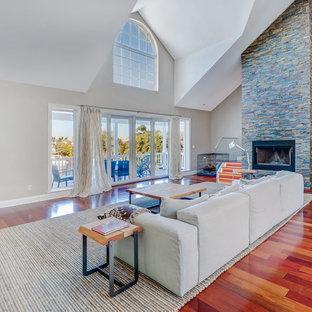 マイアミの大きいビーチスタイルのおしゃれなLDK (フォーマル、ベージュの壁、レンガの床、標準型暖炉、コンクリートの暖炉まわり、据え置き型テレビ、茶色い床) の写真