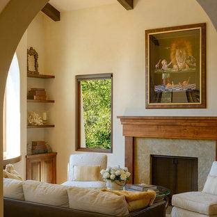 Modelo de salón mediterráneo, pequeño, con paredes beige, suelo de madera clara, chimenea tradicional y marco de chimenea de piedra