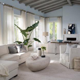 サンタバーバラの中サイズのビーチスタイルのおしゃれなLDK (青い壁、淡色無垢フローリング、標準型暖炉、フォーマル、漆喰の暖炉まわり、テレビなし) の写真
