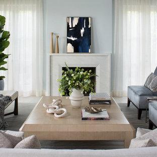Modelo de salón para visitas abierto, marinero, de tamaño medio, sin televisor, con paredes azules, suelo de madera clara, chimenea tradicional y marco de chimenea de yeso