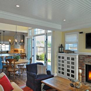 Immagine di un grande soggiorno american style aperto con pareti gialle, parquet chiaro, camino classico, cornice del camino in mattoni, TV a parete e pavimento marrone