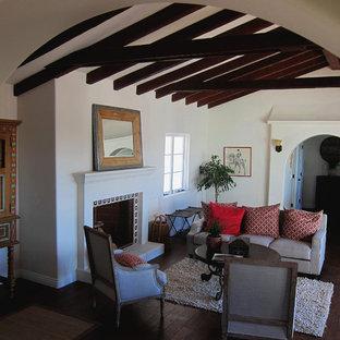サンタバーバラの小さい地中海スタイルのおしゃれなLDK (白い壁、無垢フローリング、標準型暖炉、タイルの暖炉まわり、テレビなし、茶色い床) の写真