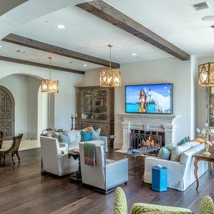 Aménagement d'un grand salon sud-ouest américain ouvert avec un mur blanc, un sol en bois brun, une cheminée standard, un manteau de cheminée en pierre et un téléviseur fixé au mur.