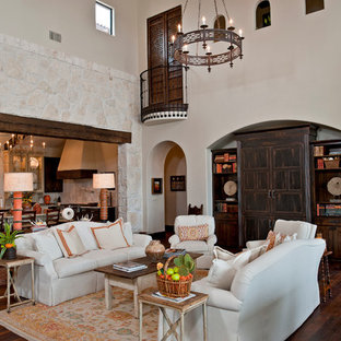 Example of a huge tuscan formal and open concept medium tone wood floor living room design in Austin with white walls, a standard fireplace and a stone fireplace
