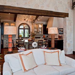 Cette photo montre un très grand salon méditerranéen ouvert avec une salle de réception, un mur blanc, un sol en bois brun, une cheminée standard et un manteau de cheminée en pierre.