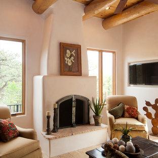 Cette photo montre un salon sud-ouest américain de taille moyenne et ouvert avec une salle de réception, un mur beige, une cheminée standard, un manteau de cheminée en plâtre et un téléviseur fixé au mur.