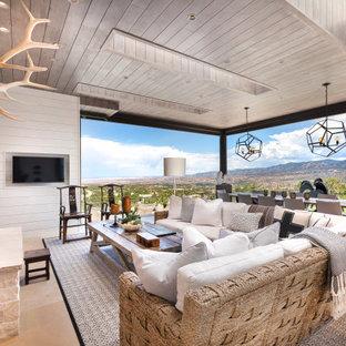 Стильный дизайн: гостиная комната в стиле фьюжн с белыми стенами, стандартным камином, фасадом камина из камня, телевизором на стене и серым полом - последний тренд