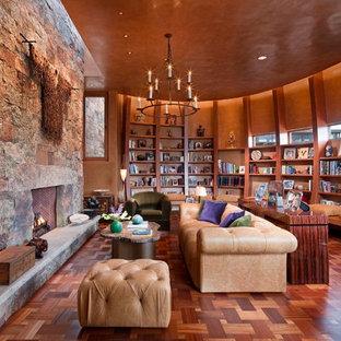Aménagement d'un très grand salon avec une bibliothèque ou un coin lecture sud-ouest américain fermé avec un mur orange, une cheminée standard, un sol en bois foncé, un manteau de cheminée en pierre, aucun téléviseur et un sol marron.