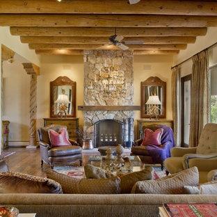 Immagine di un soggiorno american style di medie dimensioni e aperto con sala formale, pareti beige, parquet scuro, camino classico, cornice del camino in pietra, nessuna TV e pavimento marrone