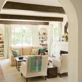 Неиссякаемый источник вдохновения для домашнего уюта: большая изолированная гостиная комната в средиземноморском стиле с белыми стенами, полом из терракотовой плитки и стандартным камином