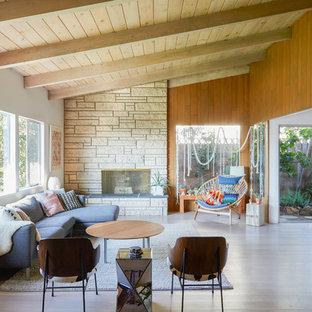 Offenes Mid-Century Wohnzimmer mit Kaminumrandung aus Stein, weißer Wandfarbe, hellem Holzboden, Gaskamin und beigem Boden in Los Angeles