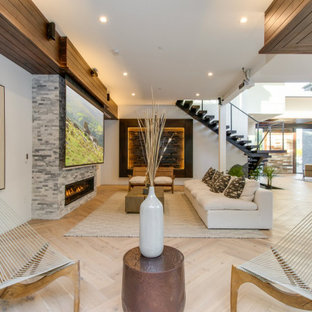 This is an example of a contemporary open concept living room in Orange County with white walls, light hardwood floors, a ribbon fireplace and beige floor.