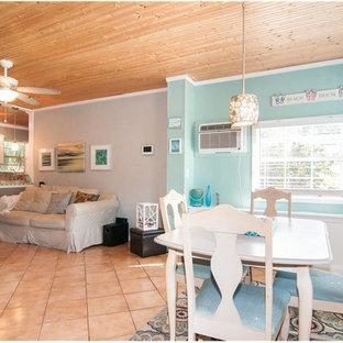 Imagen de salón abierto, costero, pequeño, con paredes grises, suelo de baldosas de cerámica, televisor colgado en la pared y suelo naranja