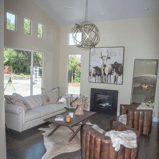 Inspiration pour un grand salon sud-ouest américain ouvert avec une salle de réception, un mur beige, un sol en bois foncé, une cheminée standard, un manteau de cheminée en métal et un sol marron.