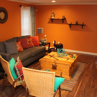 Foto di un soggiorno stile americano di medie dimensioni e chiuso con pareti arancioni, pavimento in legno massello medio, nessun camino e nessuna TV