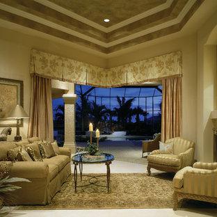マイアミの大きい地中海スタイルのおしゃれな独立型リビング (フォーマル、ベージュの壁、トラバーチンの床、標準型暖炉、漆喰の暖炉まわり、テレビなし) の写真