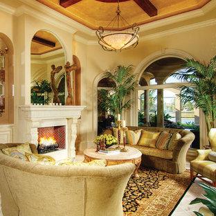 マイアミの広い地中海スタイルのおしゃれなLDK (フォーマル、ベージュの壁、トラバーチンの床、標準型暖炉、石材の暖炉まわり、テレビなし) の写真