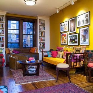 Exemple d'un salon éclectique de taille moyenne et ouvert avec un mur jaune et un sol en bois foncé.