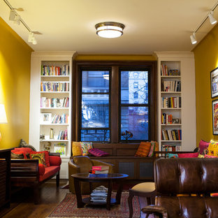 Design ideas for a mid-sized eclectic enclosed living room in New York with a library, yellow walls and dark hardwood floors.