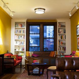Aménagement d'un salon avec une bibliothèque ou un coin lecture éclectique de taille moyenne et fermé avec un mur jaune et un sol en bois foncé.