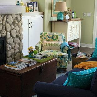 グランドラピッズの小さいビーチスタイルのおしゃれなリビング (緑の壁、無垢フローリング、標準型暖炉、石材の暖炉まわり、壁掛け型テレビ) の写真