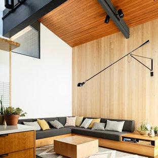 Offenes Mid-Century Wohnzimmer mit weißer Wandfarbe, dunklem Holzboden und braunem Boden in Portland