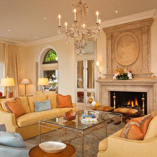 Immagine di un grande soggiorno chic aperto con pareti beige, camino classico, sala formale, cornice del camino in pietra, nessuna TV, pavimento in travertino e pavimento beige