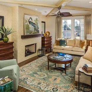 Repräsentatives, Abgetrenntes Maritimes Wohnzimmer mit gelber Wandfarbe, dunklem Holzboden, Gaskamin und Kaminumrandung aus Backstein in Atlanta