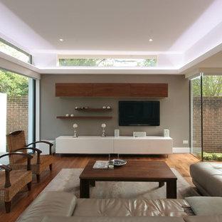 Inspiration för ett mellanstort funkis separat vardagsrum, med ett finrum, beige väggar, mellanmörkt trägolv och en väggmonterad TV