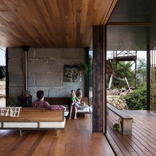 Imagen de salón moderno con suelo de madera en tonos medios y estufa de leña