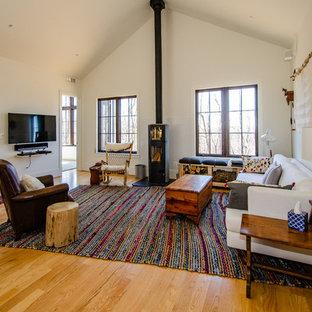 ワシントンD.C.の巨大な北欧スタイルのおしゃれなLDK (白い壁、薪ストーブ、壁掛け型テレビ) の写真