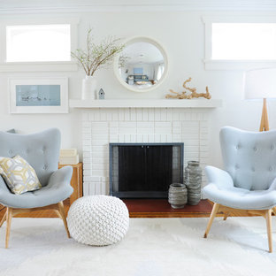 バンクーバーの中サイズのビーチスタイルのおしゃれなLDK (白い壁、無垢フローリング、標準型暖炉、レンガの暖炉まわり、フォーマル、テレビなし) の写真