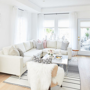 This is an example of a small scandinavian open concept living room in Toronto with white walls, limestone floors, a standard fireplace, a wood fireplace surround and a built-in media wall.